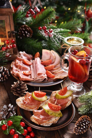 Christmas table with served mini canapes with parma ham, platter of sliced meats and cranberry compote