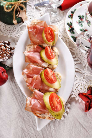 Christmas table with served mini canapes with parma ham, pickled cucumber and tomato-top view Stok Fotoğraf
