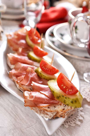 Christmas table with served mini canapes with parma ham, pickled cucumber and tomato