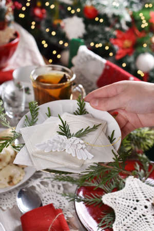 hand of woman holding Christmas Eve wafer at the festive table with traditional dishes