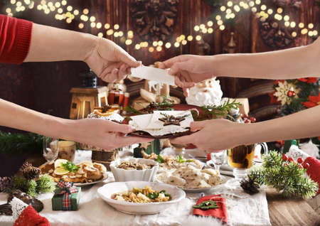 family sharing Christmas Eve wafer at the festive table with traditional dishes