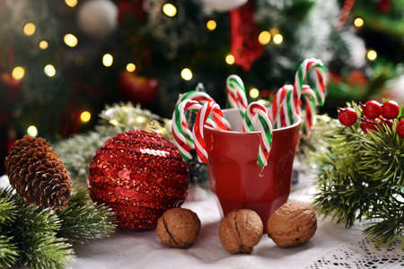 Christmas decoration with candy canes in red mug and the ornament in front of Christmas tree