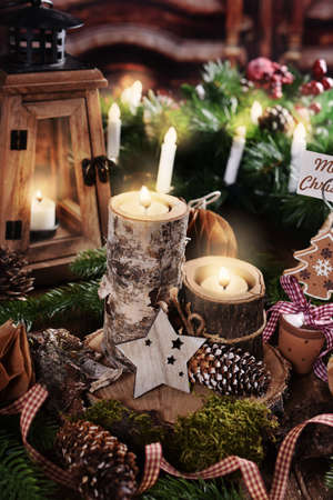 moody Christmas arrangement with candles in wooden holders, lantern, paper ornaments and decors in rustic style
