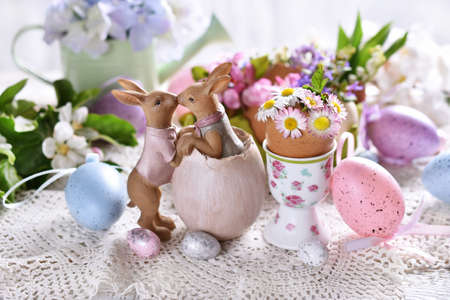 Easter decoration with funny kissing bunnies figurine and spring flowers in egg shells on festive table