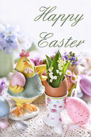 Easter greeting card with funny hen figurine and spring flowers in egg shells on festive table