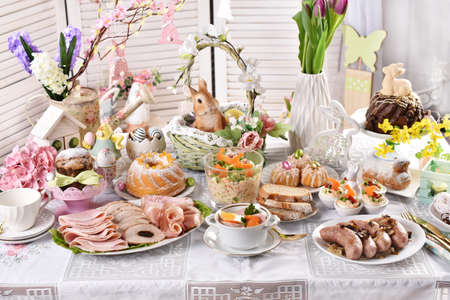 traditional Easter dishes with white borscht, sausage, eggs, salad and cakes on festive table in Poland