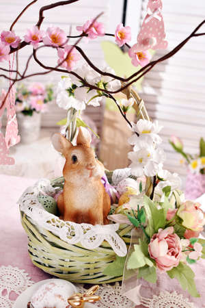 Easter wicker basket with floral decoration and cute bunny figurine and eggs on festive table