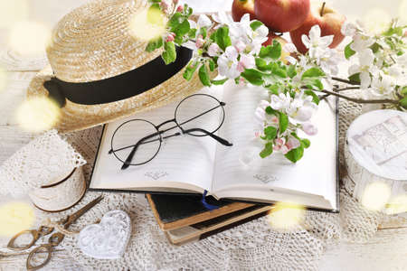 spring still life in romantic style with apple blossom branches, glasses and straw hat on old books