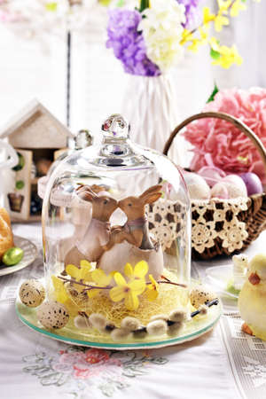 Easter table decoration with kissing bunnies in glass cloche