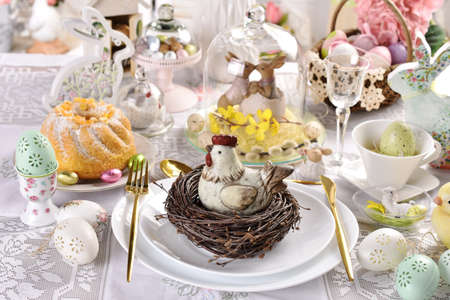 Easter table decoration with hen figurine in the nest on the plate, ring cake and decors in glass closhe