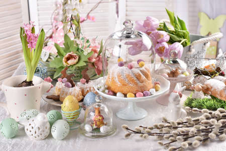 Easter table in pastel colors with ring cake and decors under a glass cloche