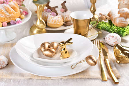 Easter table setting with golden color decors on elegant plate and cutlery in glamor style