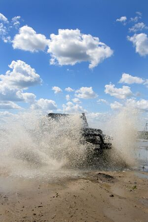 mud pit: The car overcomes a water barrier Stock Photo
