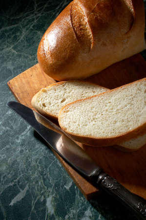 White loaf and knife on a marble kitchen table photo