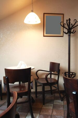 Table and chairs under a lamp in cafe photo