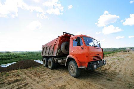 big bin: Red dumper on a under construction road