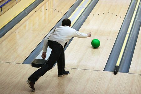 Green sphere sliding on a path in bowling photo