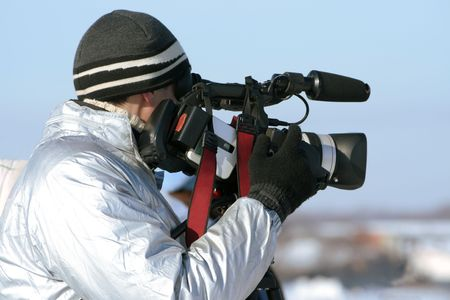 newscast: The journalist with a videocamera in the winter morning