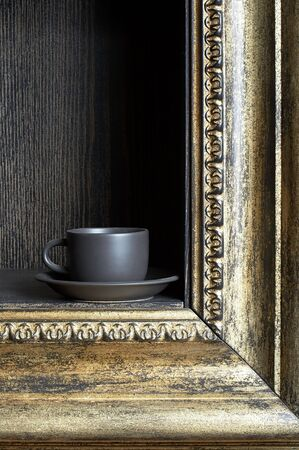 Black cup on a shelf in the form of a frame photo