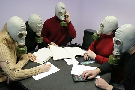 calamity: Industrial conference in gas masks behind a table Stock Photo