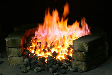 farriery: Burning black coal in the forge imposed by a brick