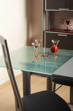 Three glasses and apple on a table in modern kitchen photo