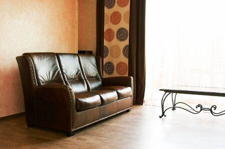 Leather sofa at a window in the modern house photo