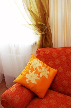 red sofa: Orange pillow with an ornament on a red sofa