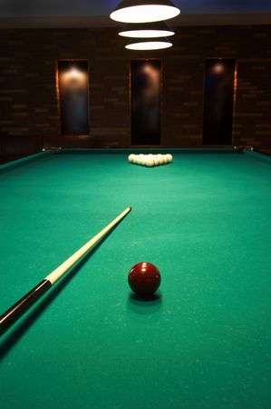 billiards room: Red sphere on a billiard table in a night club Stock Photo