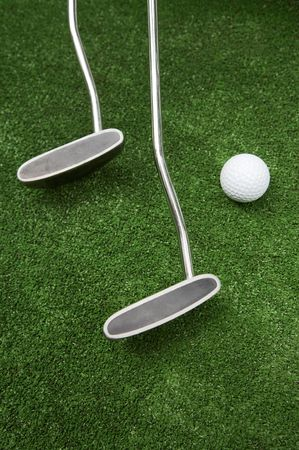 Two clubs and ball for a golf on a grass photo