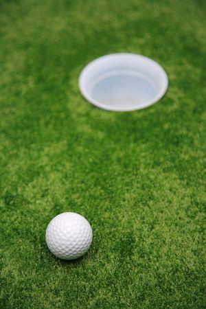 Ball and hole on a floor for a golf photo