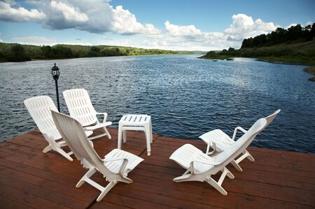 Five white armchairs and table on coast of a reservoir Stock Photo - 1297272