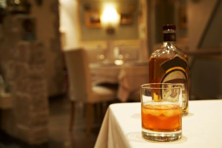 temperance: Glass from whisky and a bottle on a table at restaurant Stock Photo