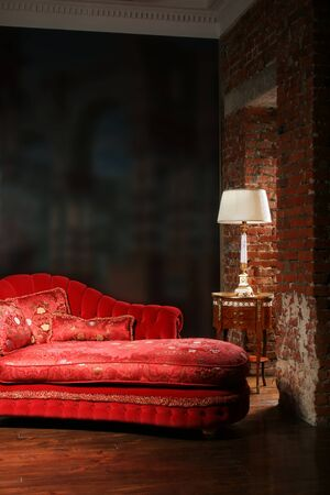 Beautiful red sofa and lamp at a wall from a brick Stock Photo
