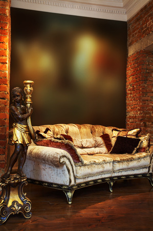 wall sconce: Ancient candlestick and sofa with pillows in an apartment