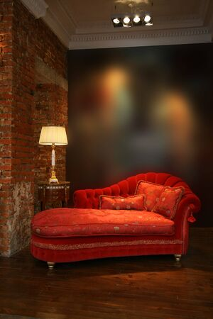 red sofa: Beautiful red sofa and lamp at a wall from a brick Stock Photo