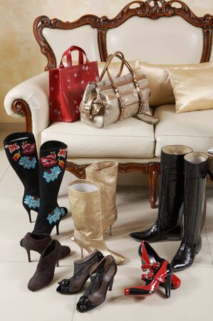 Female shoes, boots and handbags on a background of a sofa with pillows