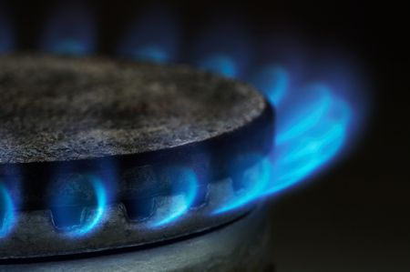 Gas burning by a dark blue flame on modern kitchen photo