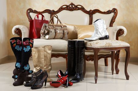 handbags: Female shoes, boots and handbags on a background of a sofa with pillows