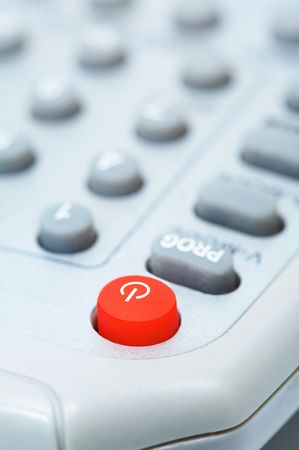 medium closeup: The red button of inclusion on a remote control