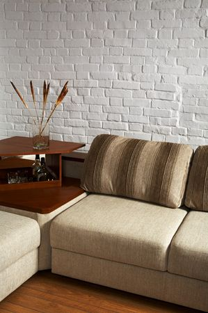 little table: Sofa and little table on a background of a brick wall Stock Photo