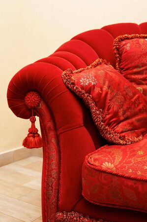 Red pillow with an ornament on a sofa photo