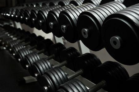 Heavy sports dumbbells in modern sports club photo
