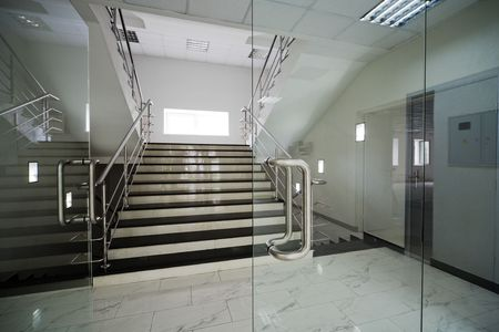 hallway: Glass doors with a kind on a marble staircase