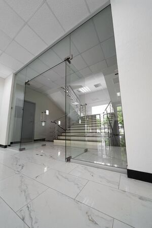 entrance door: Glass doors with a kind on a marble staircase