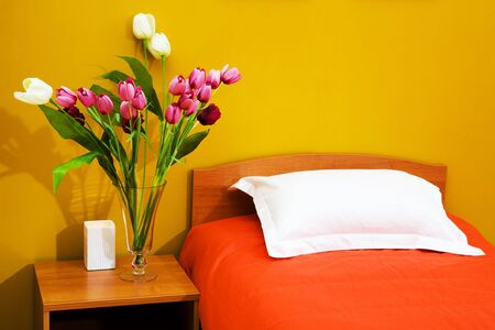 Beautiful tulips at a bed with an orange coverlet photo