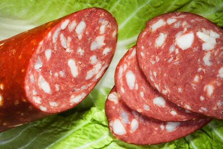 collation: Fresh sausage on a leaf of green salad