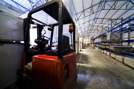 red forklift in a large modern warehouse photo