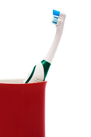 Toothbrush in a red glass on a white background photo