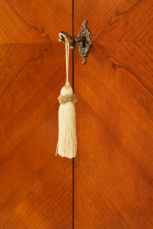 Bronze key with a tassel in a keyhole Stock Photo - 4602406